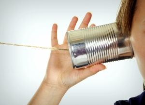 Female hand making a phone call through a can and wire