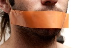 Conceptual Man with Brown Tape Over his Mouth