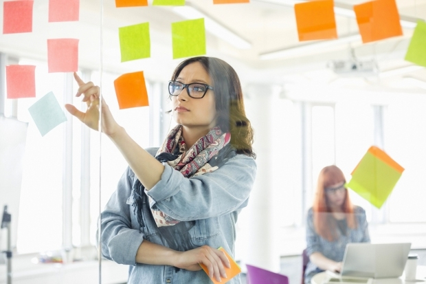 Creative businesswoman reading sticky notes on glass wall with colleague working in background at of